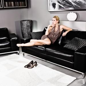 Sofa Carrera charakteryzuje się głęboką, połyskującą czernią. Siedzisko osadzone na stalowych nóżkach wygląda lekko, ale bardzo gustownie. Fot. Caya Design