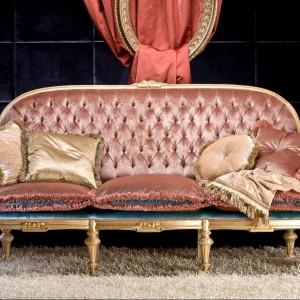 Dekoracyjne nóżki, pikowane oparcie, ozdobne poduchy oraz połyskująca tkanina obiciowa - kwintesencja stylu glamour. Fot. Exedra.