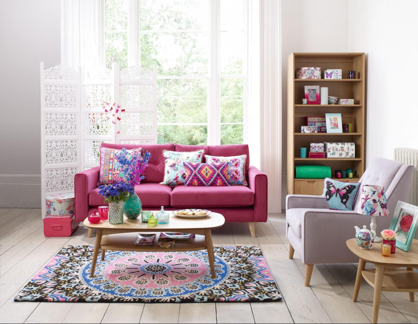 Duży pokój w mieszkaniu lubi zdecydowane barwy. Różowa sofa doskonale współgra z etnicznymi wzorami poduszek i dywanu. Jeśli odcień różu na sofie jest bardzo intensywny możemy uczynić ją jedynym, tak charakterystycznym meblem, zaś całą resztę wyposażenia skomponować w neutralnych kolorach. Fot. Debenhams