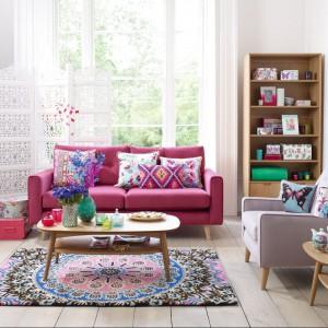 Duży pokój w mieszkaniu lubi zdecydowane barwy. Różowa sofa doskonale współgra z etnicznymi wzorami poduszek i dywanu. Fot. Debenhams