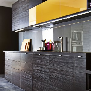 Ciemna kuchnia IKEA, rozjaśniona pomarańczowymi, górnymi frontami. Fot. IKEA