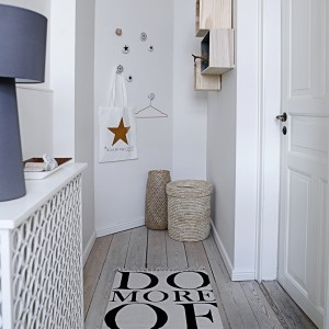 Przedpokój urządzony w stylu eko - jasna, naturalna podłoga, białe ściany i drzwi, drewniane półki, wyplatane kosze. Oferta: North&South Home. Fot. Archiwum