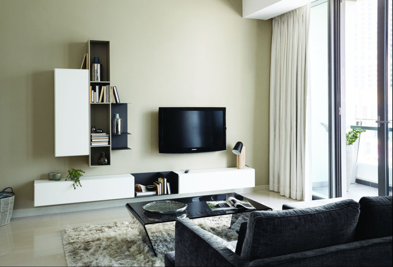 Biała, minimalistyczna meblościanka doskonale harmonizuje z szarą sofą i stolikiem z czarnego szkła. Fot. BoConcept