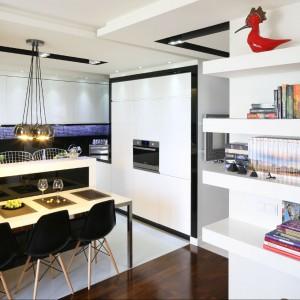 Biała kuchnia z elementami czerni to bardzo stylowa kompozycja. Warto ją podkreślić designerskimi dodatkami jak nowoczesne oświetlenie czy krzesła od znanego projektanta. Projekt: Małgorzata Mazur. Fot. Bartosz Jarosz