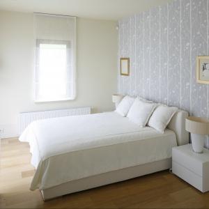 Białe łóżko ustawiono centralnie przy największej ścianie w sypialni. Stanowi ono widoczny element w pokoju, ponieważ została udekorowana tapetą. Projekt: Małgorzata Borzyszkowska. Fot. Bartosz Jarosz