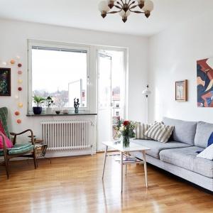 W salonie stylizowanym na skandynawski pierwszorzędną rolę grają kolorowe dodatki. Na tej aranżacji są nimi fotel i dynamiczna grafika na ścianie. Fot. Stadshem