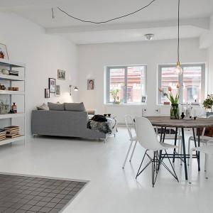 Wyróżniającym się elementem w tym salonie jest szara kanapa, a także różne krzesła ustawione przy jednym stole. To modne rozwiązanie w skandynawskich aranżacjach. Fot. Alvhem Makleri