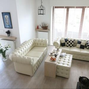 W salonie o większej powierzchni możemy sobie pozwolić na nie jedną sofę, ale nawet na dwie. W tym domu postawiono na model a\'la chesterfield. Projekt: Jarek Jończyk Monika Włodarczyk Fot. Bartosz Jarosz