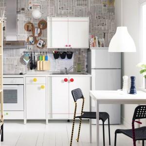 Biała kuchnia w bardzo nietypowym wydaniu. Zamiast glazury zastosowano tu tapetę imitującą gazetę, zaś kolorowe gałki skupiają wzrok każdego. Fot. IKEA