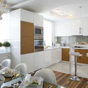 Białe fronty na wysoki połysk połączone z matowym drewnem sprawią, że kuchnia będzie nowoczesna i minimalistyczna. Projekt: Małgorzata Mazur. Fot. Bartosz Jarosz