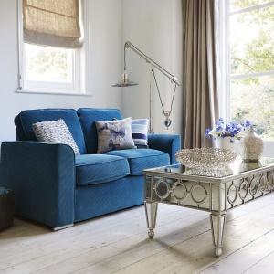 Mała sofa w turkusowym kolorze świetnie sprawdzi się w jasnym salonie. Miękkie siedzisko pozwoli na długie posiadówki, zaś kolorowe poduszki dodadzą nastrojowego wyglądu. Fot. Furniture Village
