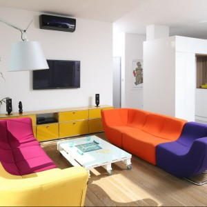 Żółta komoda i wielokolorowe sofy pięknie korespondują z białymi ścianami i urozmaicają nieco sterylne wnętrze. Projekt. Konrad Grodziński. Fot. Bartosz Jarosz
