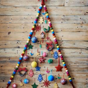 Współczesne choinki łamią dziś wszelkie zasady, jak chociażby ta - wykonana z filcowych kuleczek i zawieszona na ścianie. Można taką wykonać samemu, niekoniecznie z kulek, ale nawet z samych lampek, tworząc na ścianie zarys drzewka. Fot. Sainsburyshome