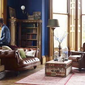 Najbardziej popularnym rodzajem sofy Chesterfield jest klasyczny niski model w kolorze orzechowego brązu. Skórzana tapicerka jest bardzo elegenacka i świetnie pasuje do industrialnych salonów. Fot. DFS