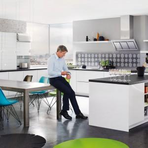 Biała kuchnia w wersji total look nie wychodzi z mody. Czarny blat kontrastujący z białymi szafkami w połysku, podkreśla kształt zabudowy. Fot. Rational