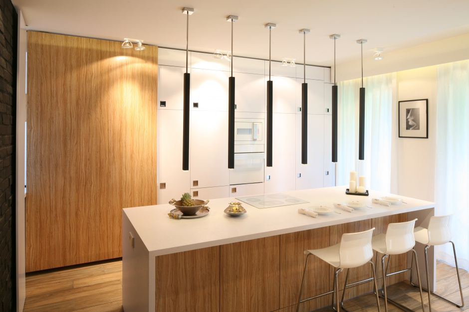 Kuchnia z wyspą wykończona drewnem. Wyspę podkreślono designerskim oświetleniem, całość prezentuje się atrakcyjnie wizualnie. Projekt: Dominik Respondek. Fot. Bartosz Jarosz
