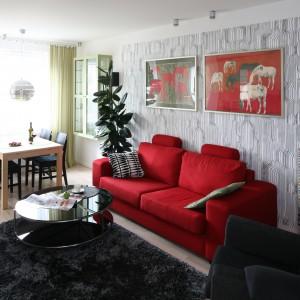 Czerwona sofa w tym wnętrzu stanowi barwną plamę na tle szarości. Projekt Marta Kruk. Fot. Bartosz Jarosz