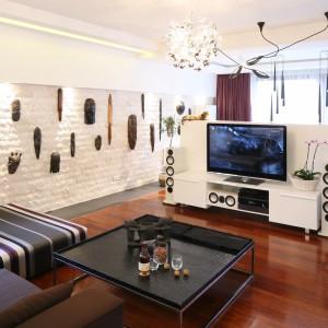 Biała ścianka telewizyjna tworząca przegrodę salonu od jadalni to rozwiązanie doskonałe do dużych wnętrz. Projekt: Katarzyna Mikulska-Sękalska. Fot. Bartosz Jarosz
