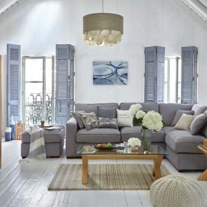 We wnętrzach w stylu marinistycznym oprócz bieli i błękitów nie może zabraknąć naturalnego drewna. Sofa w szarym kolorze doskonale współgra ze stolikiem na drewnianych nogach, o szklanym blacie. Fot. Dunelm