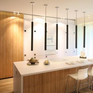 Jasne odcienie drewna doskonale korespondują w białymi frontami szafek kuchennych. Na dużych powierzchniach drewno wygląda elegancko, ponieważ widać jego rysunki i spękania. Projekt: Dominik Respondek. Fot. Bartosz Jarosz