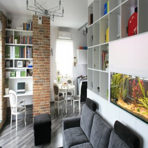 Na półki z książkami możemy zaadaptować wszelkie nietypowe miejsca i kąty, oszczędzając w ten sposób cenną przestrzeń. Projekt: Agnieszka Ludwinowska. Fot. Bartosz Jarosz