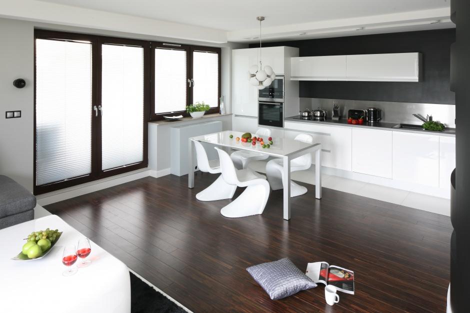 Białe meble w nowoczesnej kuchni to klasa i elegancja sama w sobie. Nie przytłaczają wnętrza i ładnie komponują się z resztą mieszkania. Projekt: Agnieszka Burzyszkowska-Walkosz. Fot. Bartosz Jarosz