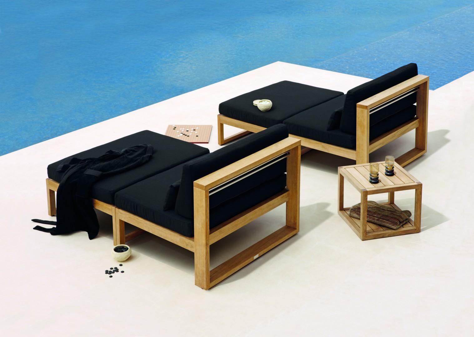 Drewniany, nowoczesny leżak z czarnym materacem prezentuje się bardzo elegancko. Fot. Manutti