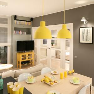 Zgrabna i lekka w formie szafka RTV, w kolorze żółtym to ciekawe urozmaicenie wnętrza utrzymanego w bieli i szarości. Projekt: Lucyna Kołodziejska. Fot. Bartosz Jarosz