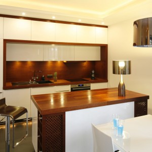 Drewno w kuchni prezentuje się bardzo naturalnie. Połączone z lakierowanymi frontami w białym kolorze będzie także eleganckie i stylowe. Projekt: Agnieszka Żyła. Fot. Bartosz Jarosz