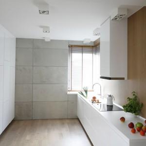 Minimalistyczną, nowoczesną kuchnię można ocieplić ścianą wykończoną w drewnie. Najlepiej sprawdzi się matowe wykończenie w lekko przygaszonym kolorze. Projekt: Agnieszka Ludwinowska. Fot. Bartosz Jarosz