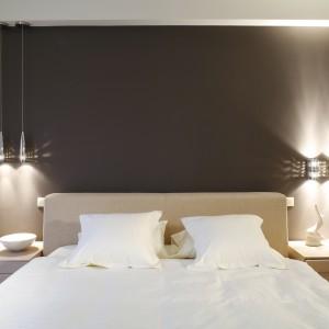 Sypialnia utrzymana w beżowej tonacji, urozmaiconej fioletem. Miękkie, tapicerowane łóżko zapewnia komfort wypoczynku. Lampki nad łóżkiem tworzą we wnętrzu klimatyczny nastrój. Projekt: Joanna Wysocka. Fot. Bartosz Jarosz