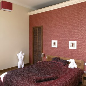 Sypialnia urządzona w beżach może wydawać się nieco mdła. W takim przypadku warto urozmaicić ją nieco, np. oryginalną tapetą we wzory. Projekt: Monika Włodarczyk, Jarosław Jończyk. Fot. Bartosz Jarosz