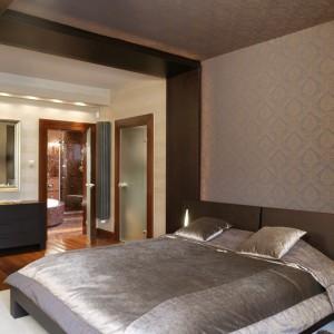 Ciemne, brązowe meble, mogą nieco przytłaczać wnętrze sypialni. W takim przypadku najlepiej postawić na jaśniejsze dodatki oraz sztuczne światło. Projekt: Julita Chrząstek. Fot. Bartosz Jarosz