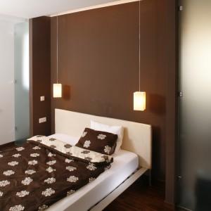 Efektownie wygląda zestawienie ciemnych brązów z różem. Ściana za łóżkiem w nasyconym odcieniu, pięknie komponuje się z jasnym łóżkiem oraz połyskującą narzutą.  Projekt: Piotr Gierałtowski. Fot. Bartosz Jarosz