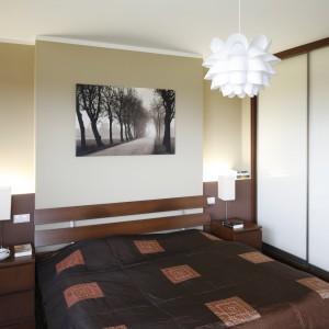 Przestrzenny obraz nad łóżkiem wizualnie powiększa wnętrze. Łóżko z dekoracyjnym, drewnianym zagłówkiem zapewnia komfort wypoczynku. Projekt: Piotr Stanisz. Fot. Bartosz Jarosz