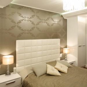 Sypialnia jest przytulna dzięki zastosowaniu ciepłej kolorystyki na ścianach. Szafki pod sam sufit ulokowane po obu stronach łóżka zapewniają dużo miejsca do przechowywania. Projekt: Karolina Łuczyńska. Fot. Bartosz Jarosz