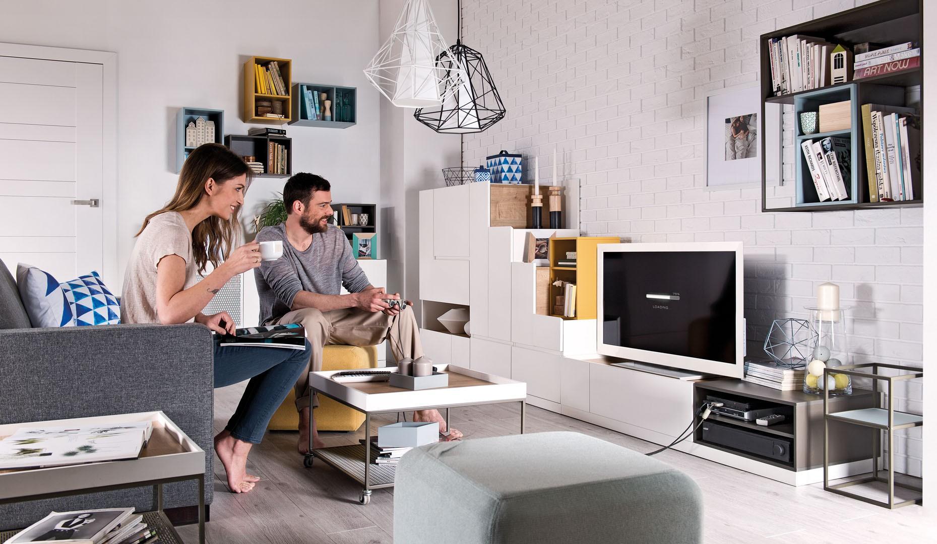 Szafka RTV z kolekcji Muto, wykonana z białej płyty w matowym kolorze. Drewniane korpusy ocieplają całość aranżacji. Fot. Meble Vox