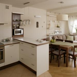 Kuchnia otwarta na salon utrzymana jest w jasnej tonacji. Białe matowe meble świetnie współgrają z białym ścianami oraz meblami. Wnętrze wydaje się bardzo przestronne. Projekt: Lucyna Stefaniak. Fot. Bartosz Jarosz