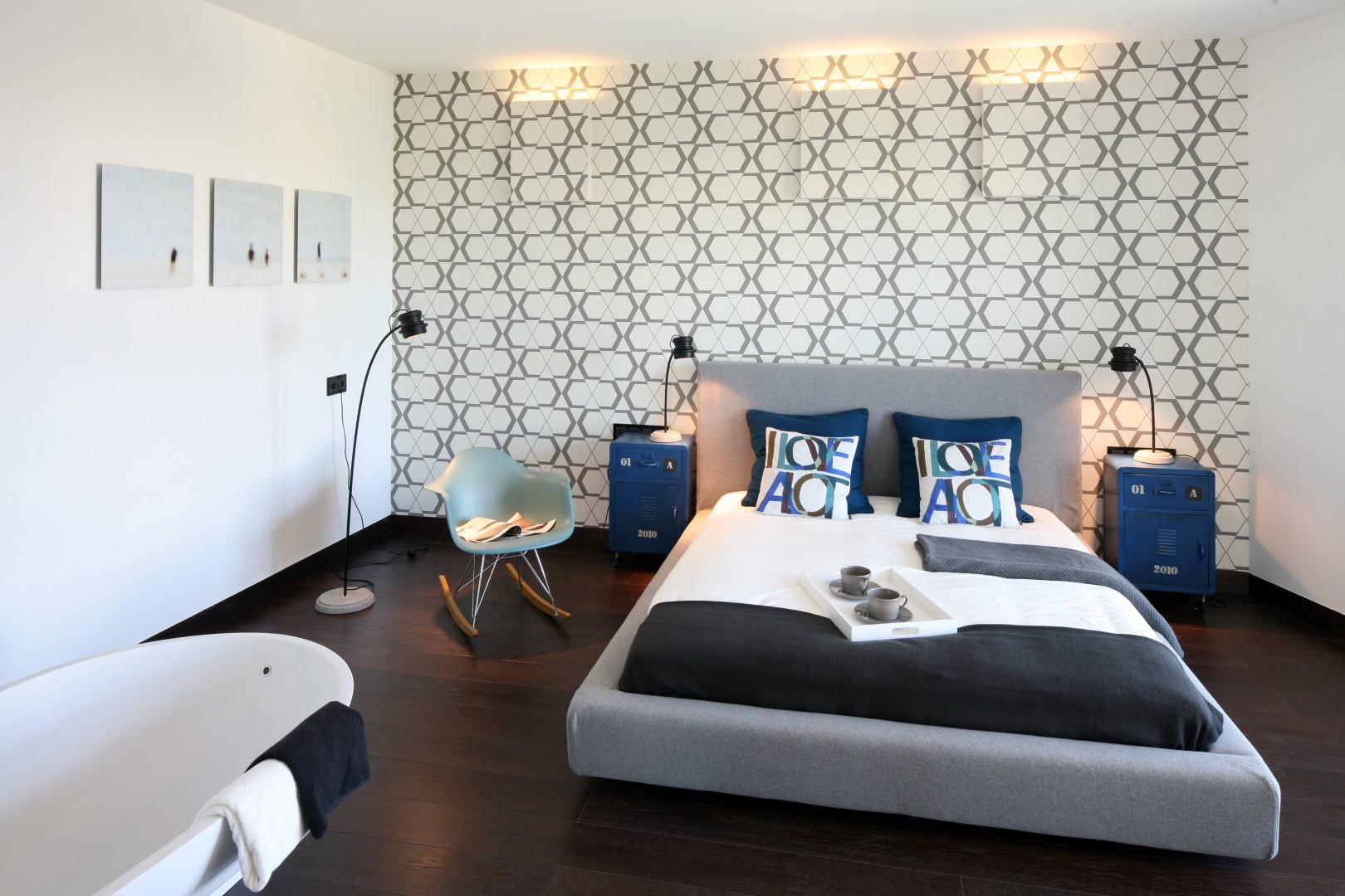 Szare tapicerowane łóżka to najnowszych krzyk mody. Mebel w zestawieniu z niebieskimi szafkami nocnymi prezentuje się bardzo gustownie. Projekt: Justyna Smolec. Fot. Bartosz Jarosz
