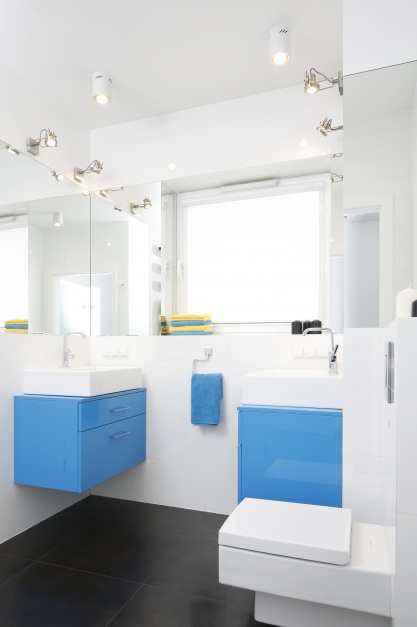 Jasna łazienka, pełna światła. Niebieskie meble pięknie urozmaicają wnętrze. Projekt: Katarzyna Uszok-Adamczyk. Fot. Bartosz Jarosz