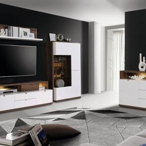 Alcano to ciepły, dębowy dekor z wyraźnym rysunkiem drewna, który kontrastuje z połyskującą bielą, subtelnie rozświetlającą wnętrze. Przydymione szkło szklanych frontów nadaje wnętrzom witryn dyskretnej elegancji. Fot. Meble Forte