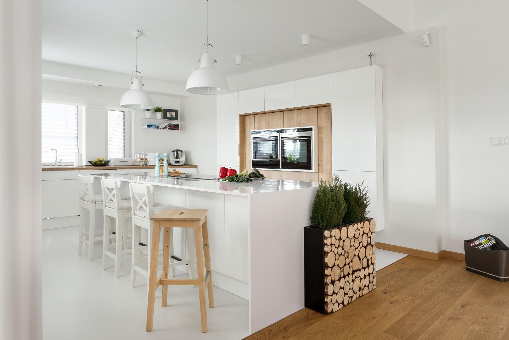 Biała kuchnia w minimalistycznym stylu. Wyspa pełni rolę miejsca gotowania i przygotowywania posiłków. Umieszczono w niej okap montowany na blacie .Projekt: Małgorzata Błaszczak. Fot. Artur Krupa