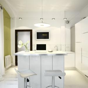 Biała kuchnia z małą wyspą, która służy jako miejsce spożywania posiłków, a także dodatkowy blat roboczy. Projekt: Liliana Masewicz-Kowalska. Fot. Tomasz Onufryjuk