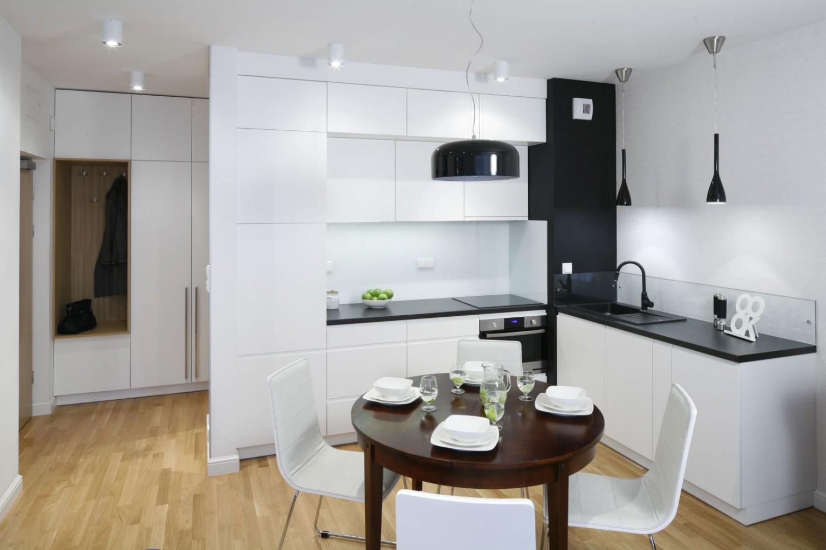 Jasna kuchnia w kształcie litery L to doskonała propozycja do małego mieszkania, gdzie przestrzeń kuchenna połączona jest z dzienną. W tym wnętrzu nowoczesność łączy się z klasyką. Projekt: Ewa Para. Fot. Bartosz Jarosz