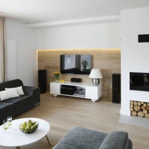 Jeśli w salonie jest kominek, dobrze jest umiejscowić telewizor w pewnej odległości od niego. Projekt Małgorzata Galewska. Fot. Bartosz Jarosz