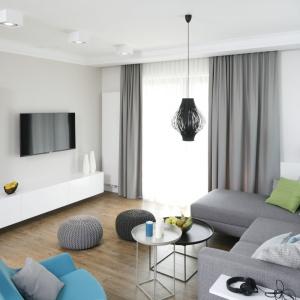 Fotel w kolorze turkusowym oraz szare pufy podkreślają styl wnętrza oraz dodają mu przytulności. Projekt: Małgorzata Galewska. Fot. Bartosz Jarosz
