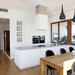 Biała kuchnia w nowoczesnym wręcz minimalistycznym stylu. Całość wizualnie ociepla drewniany stół oraz stylowe krzesła. Wyspa ze strefą gotowania pozwala przygotowywać posiłek twarzą do gości. Fot. Studio Prostych Form