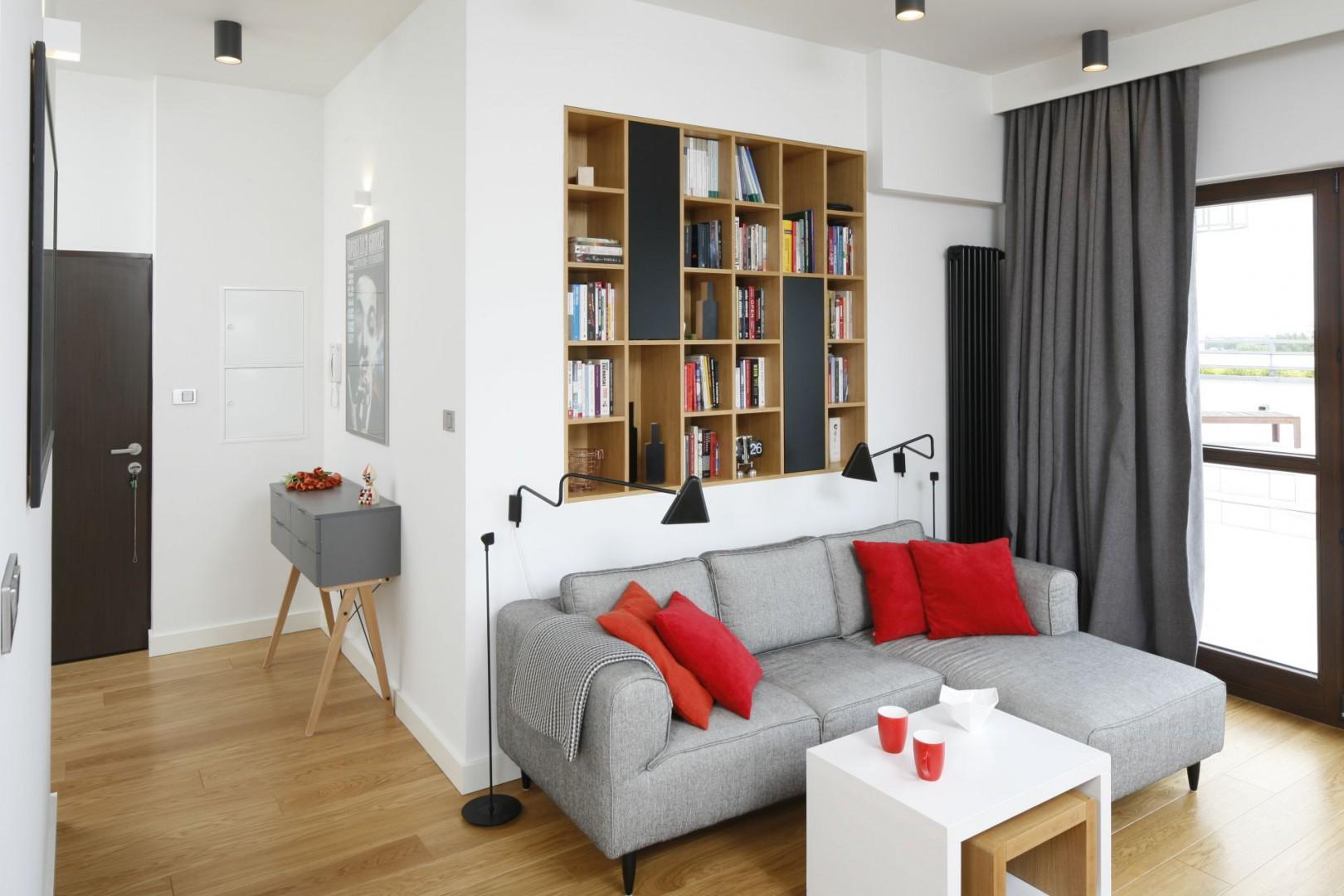 Czerwone poduchy na sofie ożywiają wnętrze. Projekt: Małgorzata Łyszczarz. Fot. Bartosz Jarosz