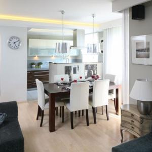 Jadalnia stanowi umowną granice między kuchnią, a salonem. Drewniany stół zestawiono z tapicerowanymi krzesłami, dzięki temu całość prezentuje się lekko i stylowo. Projekt: Małgorzata Galewska. Fot. Bartosz Jarosz