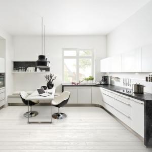 Biała kuchnia oryginalnie wygląda w połączeniu z blatem z rysunkiem kamienia. Na zdjęciu kuchnia Soft Lack. Fot. Nolte